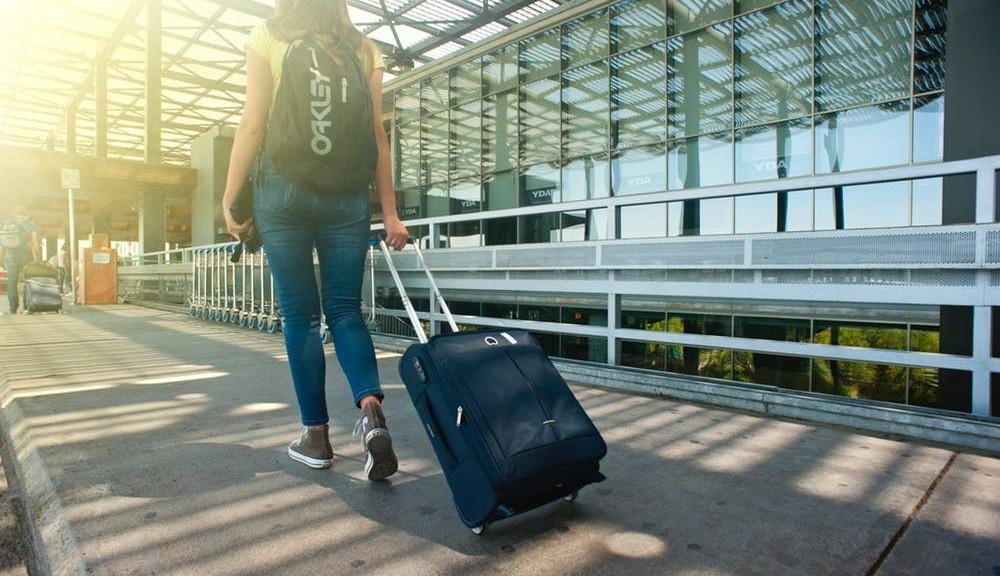 ragazza con valigia in partenza